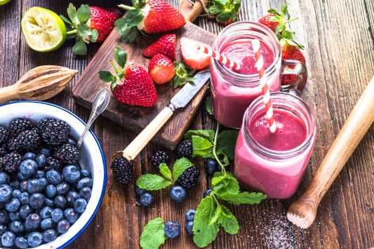 blueberries strawberries and raspberries on brown wooden surface